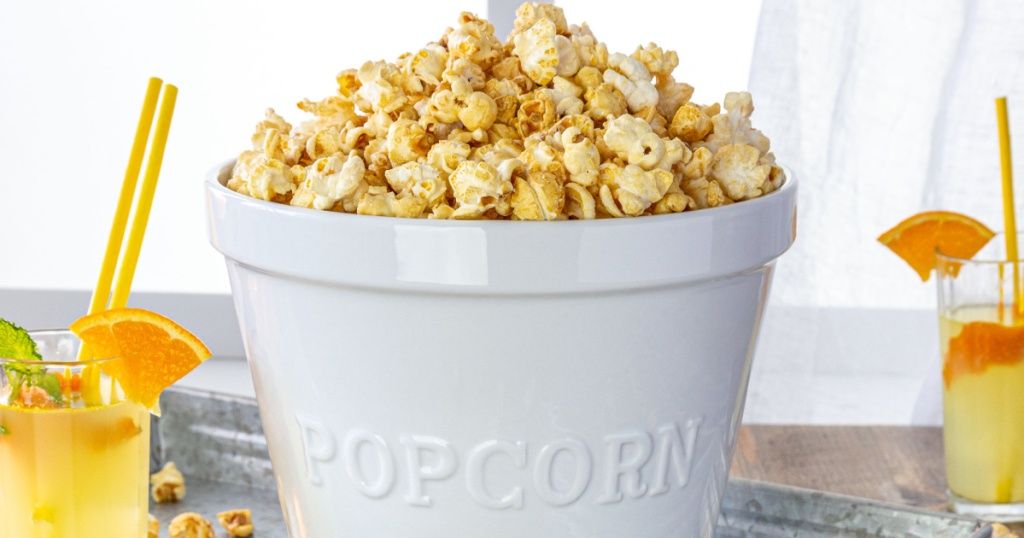 large white popcorn bowl filled with popcorn and two orange drinks