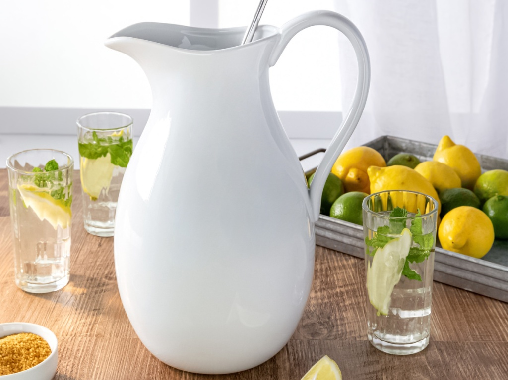 large white pitcher on table with cups and cut up lemons and limes