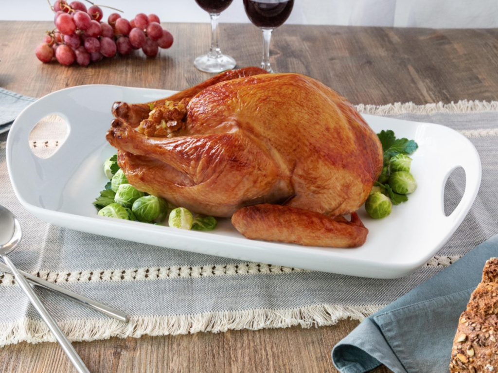 cooked turkey and vegetables on large white serving platter on dining room table