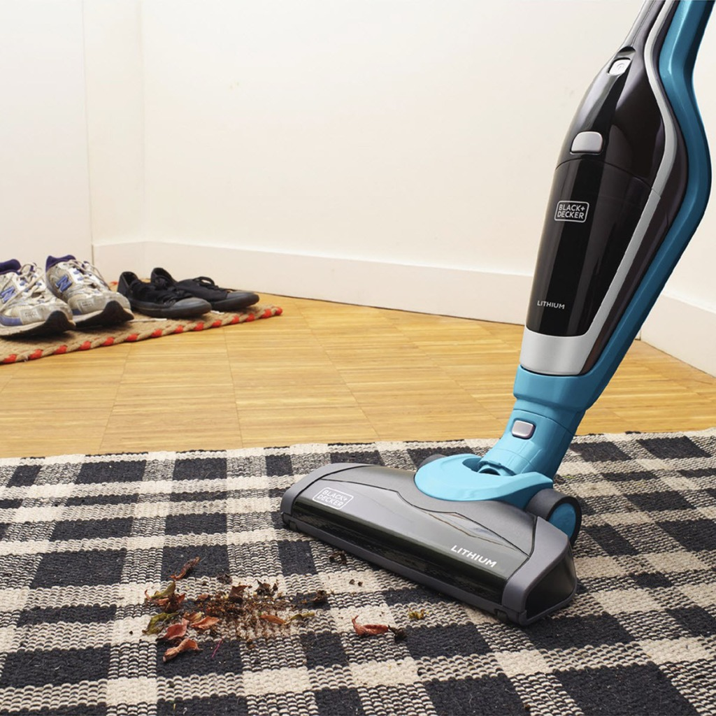 Black & Decker 2-in-1 Cordless Vacuum vacuuming up debris on plaid rug