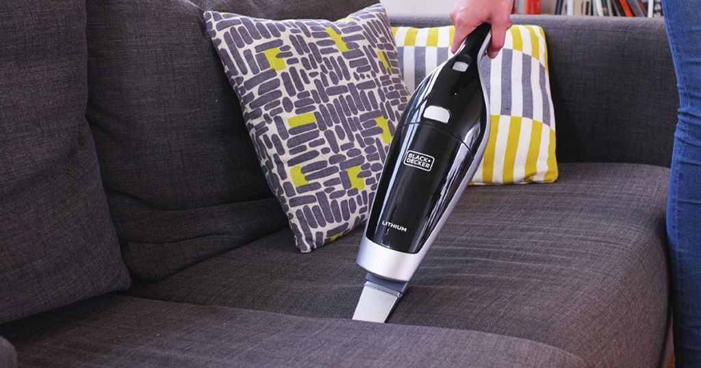 hand holding the handheld part of Black & Decker 2-in-1 Cordless Vacuum on couch
