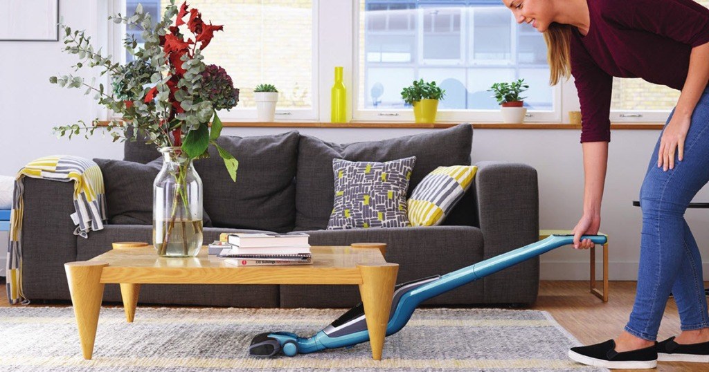 woman vacuuming under table with Black & Decker 2-in-1 Cordless Vacuum