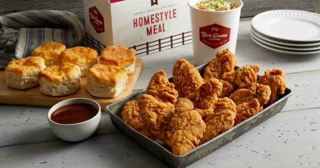 A large family sized meal of chicken, biscuits, and coleslaw near takeout container