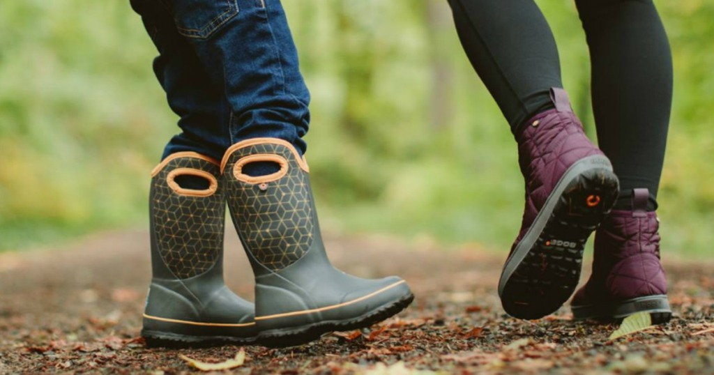 a child and adult walking in the woods and you can just see their feet