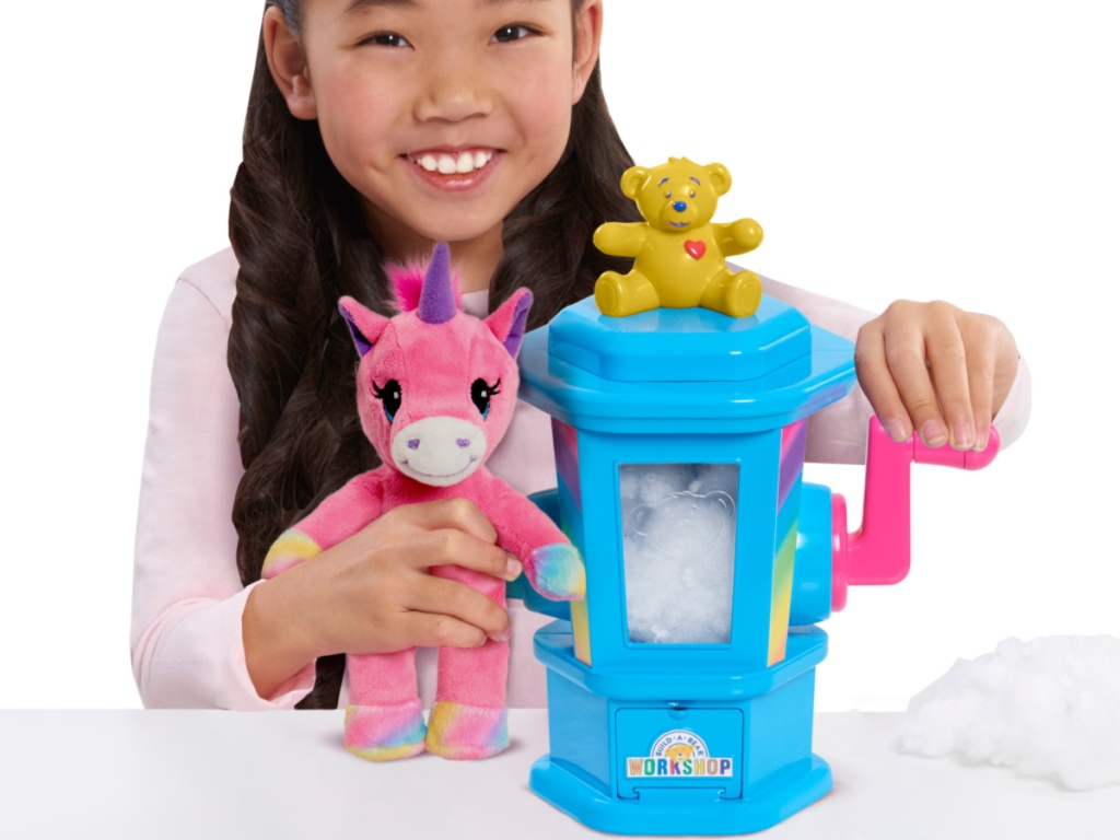 girl using hand crank on stuffing station and holding unicorn plush in other hand
