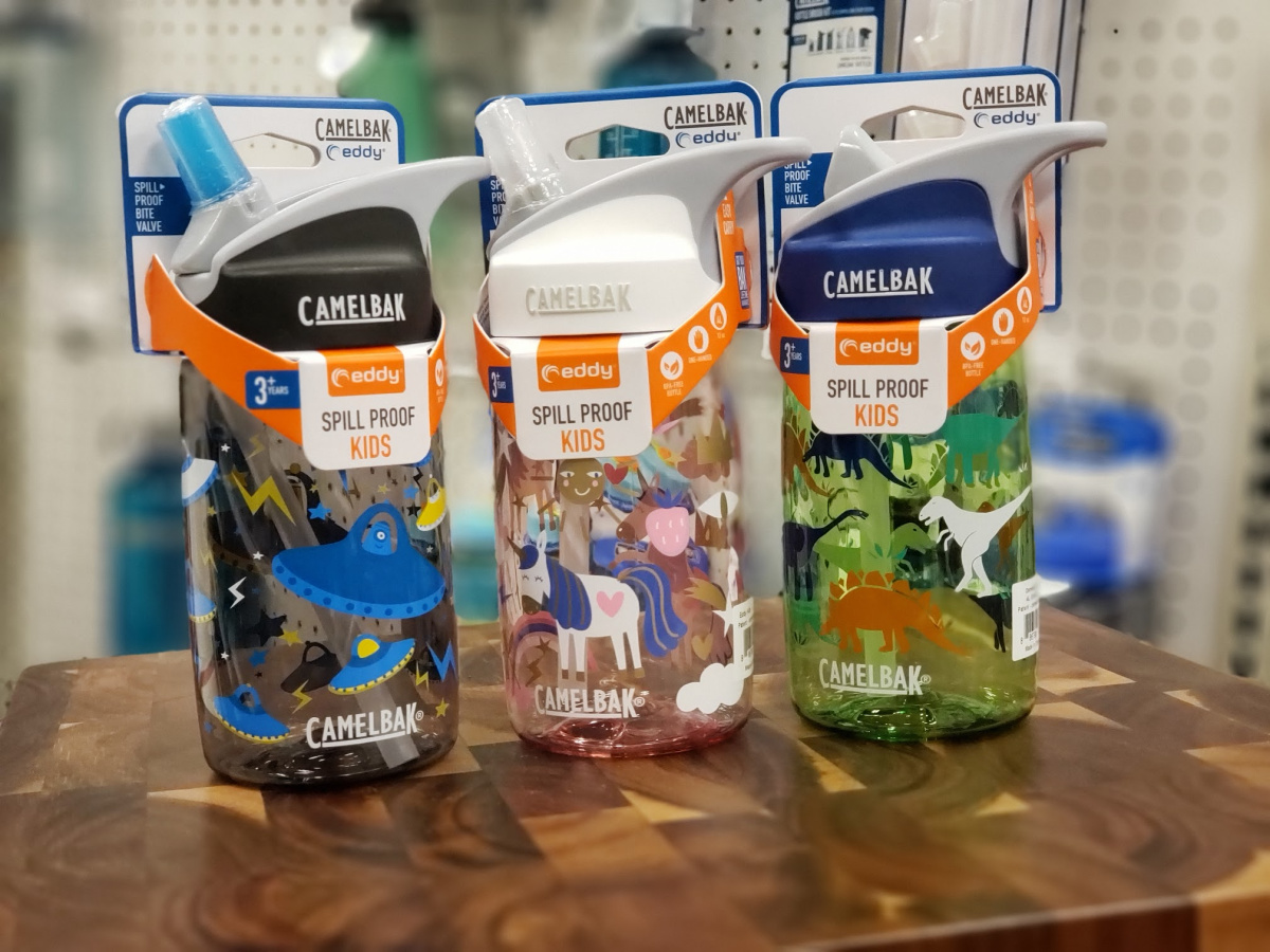 3 small camelbak water bottles on wood surface