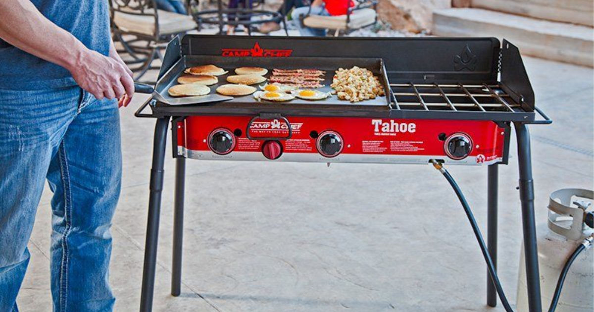man cooking on Camp Chef Tahoe 3-Burner Propane Camp Stove with Griddle