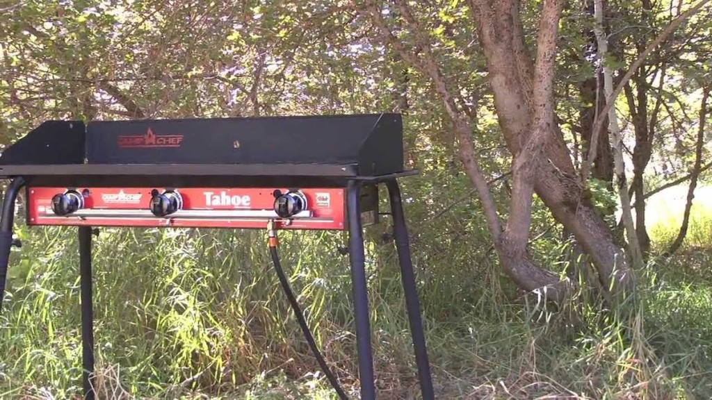 man cooking on Camp Chef Tahoe 3-Burner Propane Camp Stove with Griddle outside in the woods