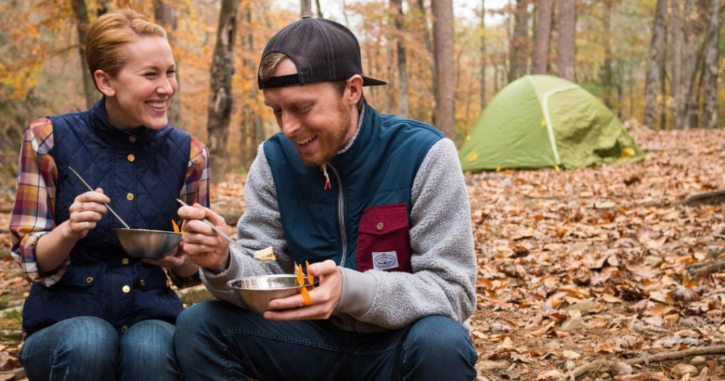 Couple eating out of bowls outside, with tent in background