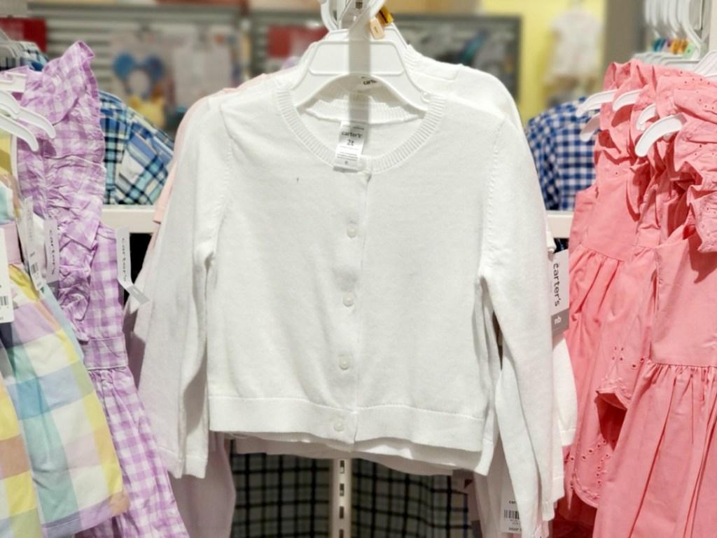 White cardigan for toddler girls on hanger in-store