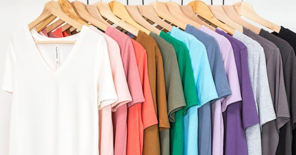 fifteen t-shirts hanging on wooden hangers