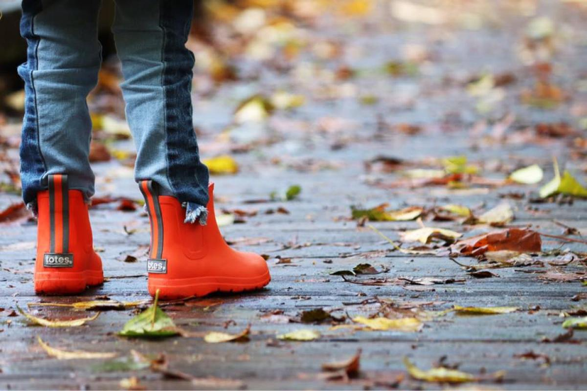 Kid wearing Cirrus Chelsea Kids Rainboots on leafy sidewalk