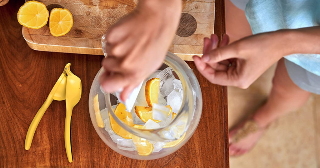 Woman standing over counter making lemonade with citrus squeezer