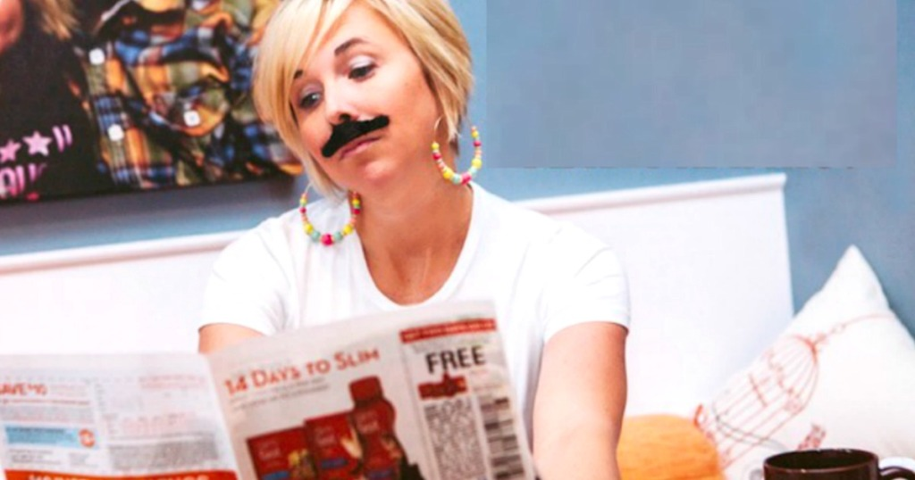 woman with mustache looking at newspaper with coupons