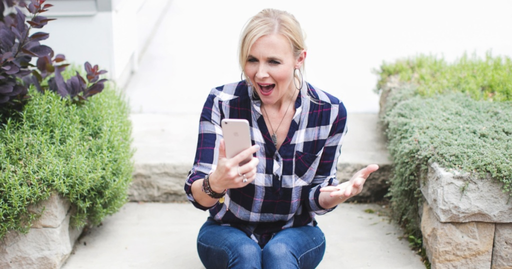 woman sitting on curb outside house using cell phone