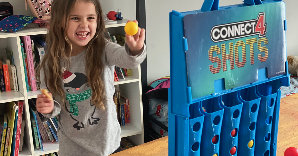 Little girl shooting ball into Connect 4 Shots game