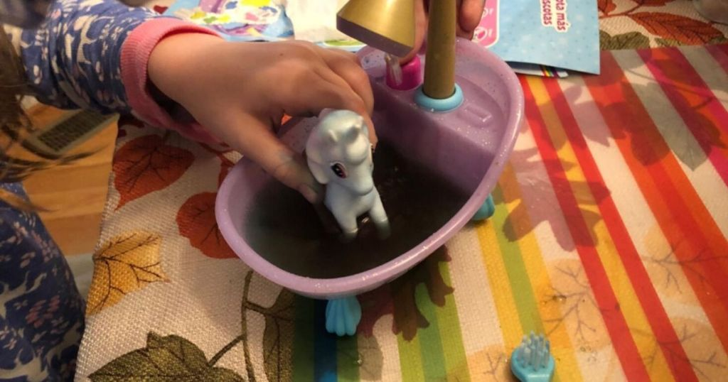little girls hand playing in a little toy tub with a little unicorn figure