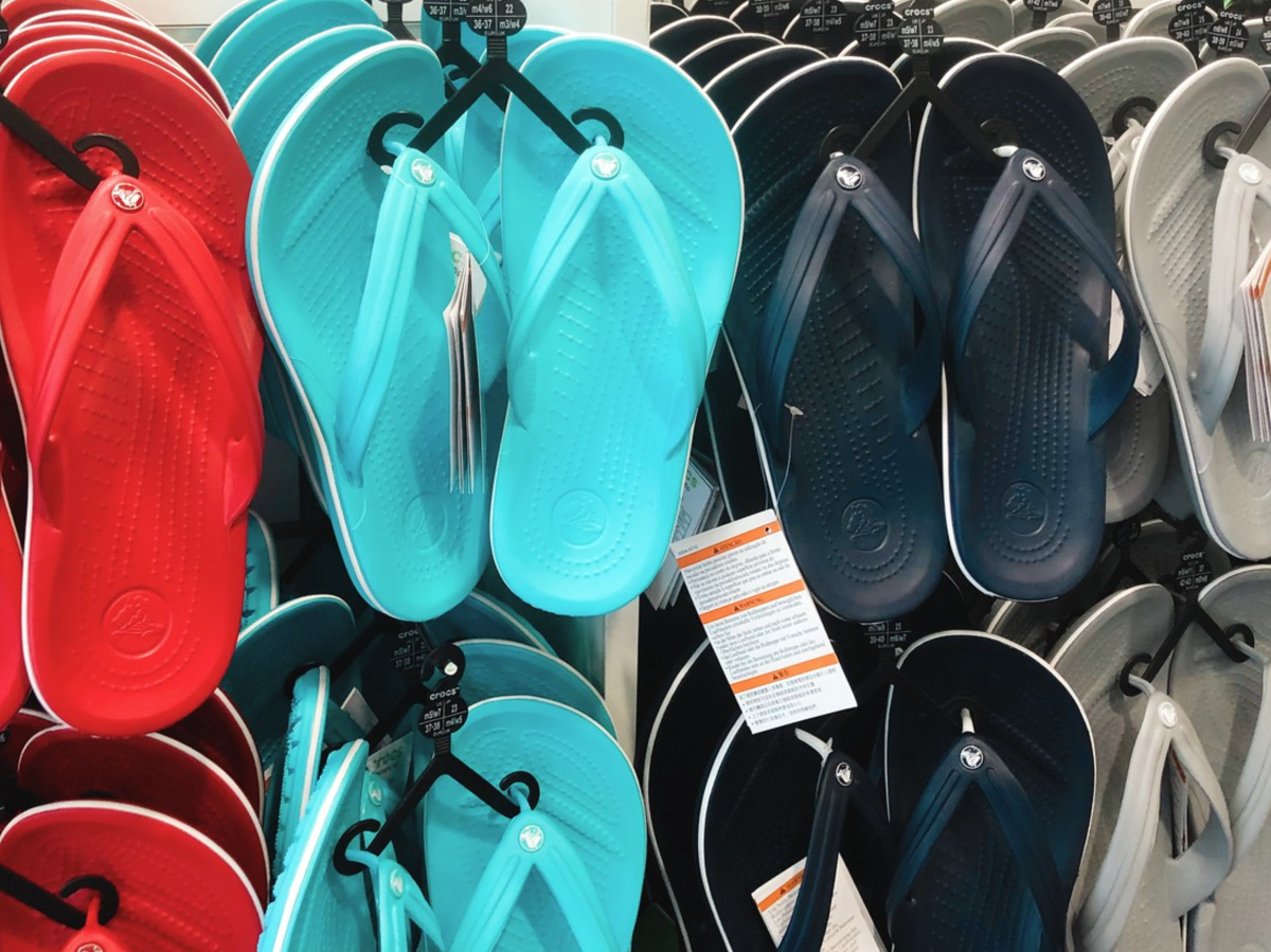 red, blue, black, and grey flip flops hanging in store