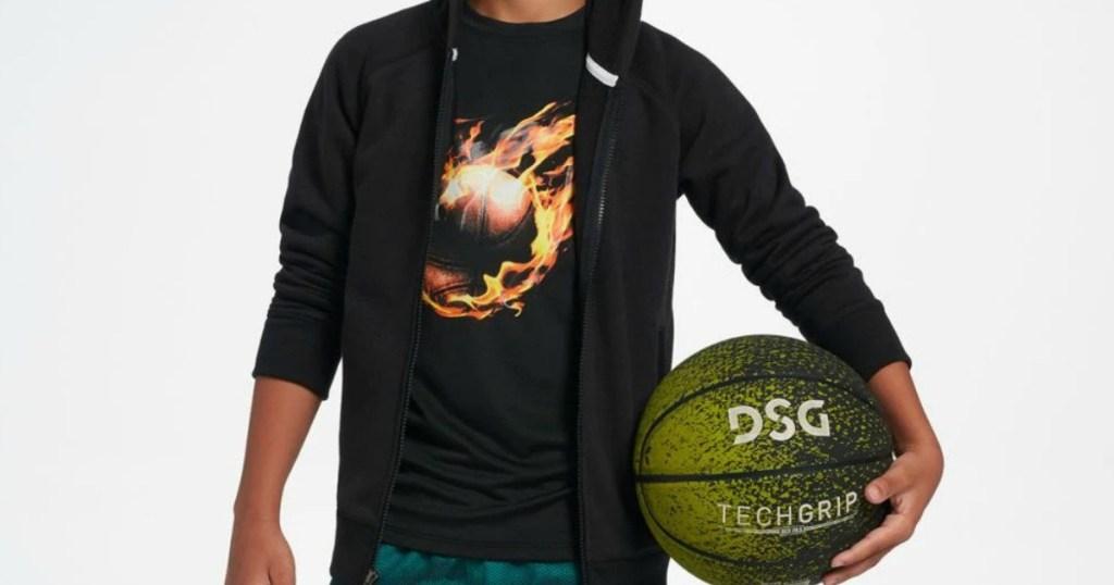 boy wearing a sweatshirt and holding a basketball
