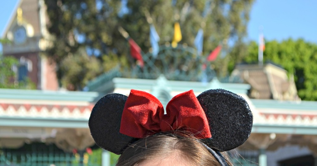 Girl wearing Mickey Ears with red bow at Disneyland