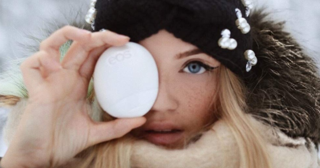 woman holding eos lotion up to her eye