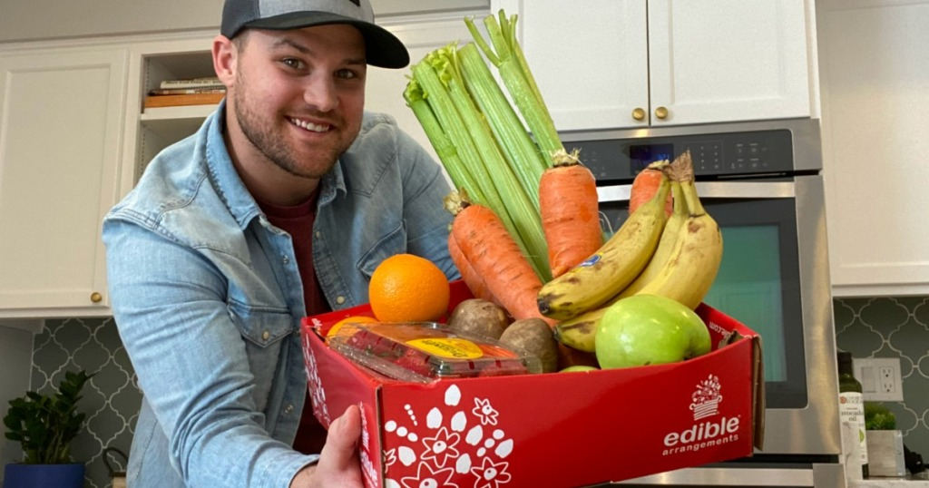 man holding a box with fruit and vegetables