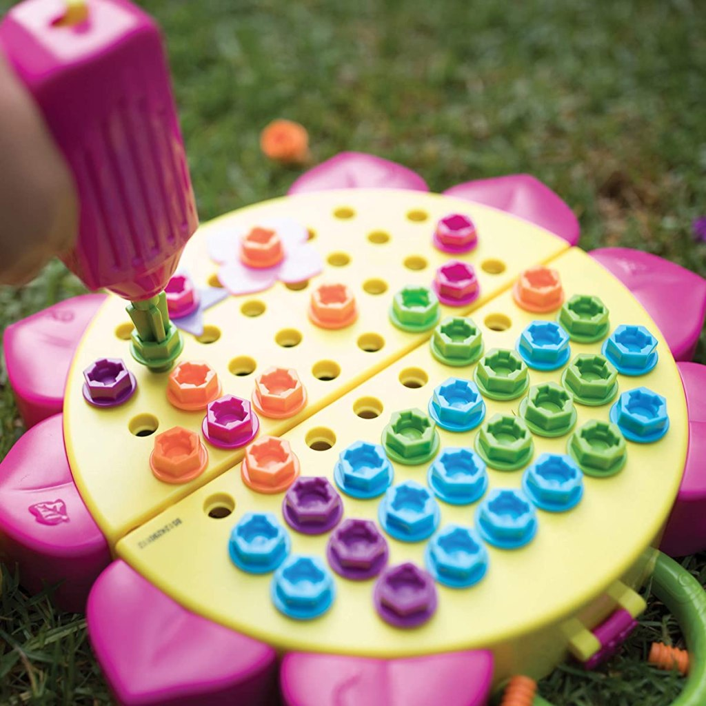 kid playing with a drill set on a flower board