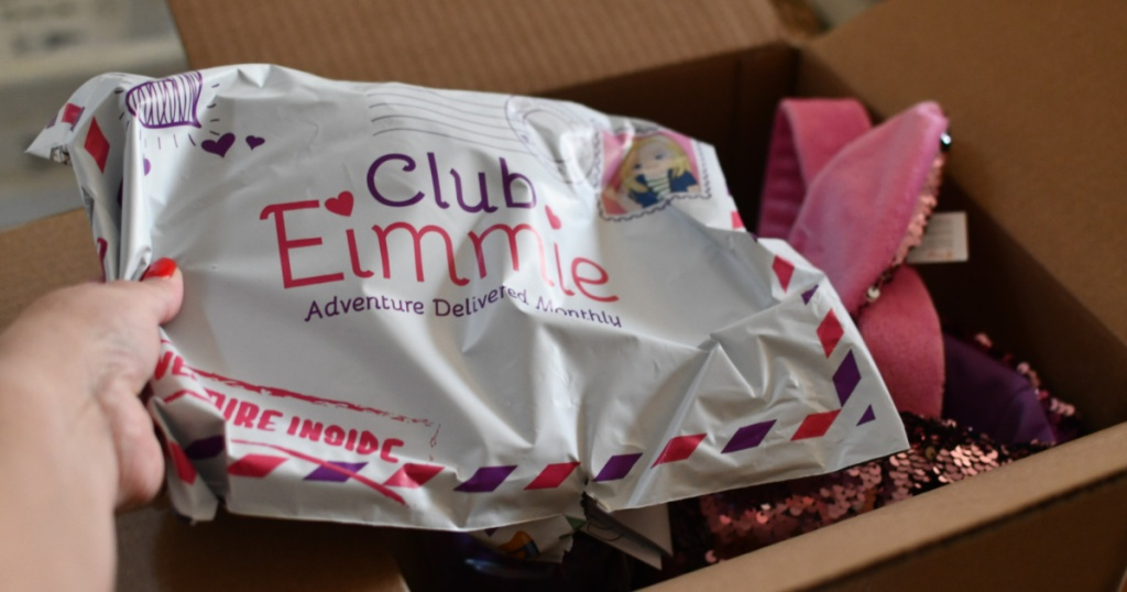 hand holding Club Eimmie Packaging with contents in box in background