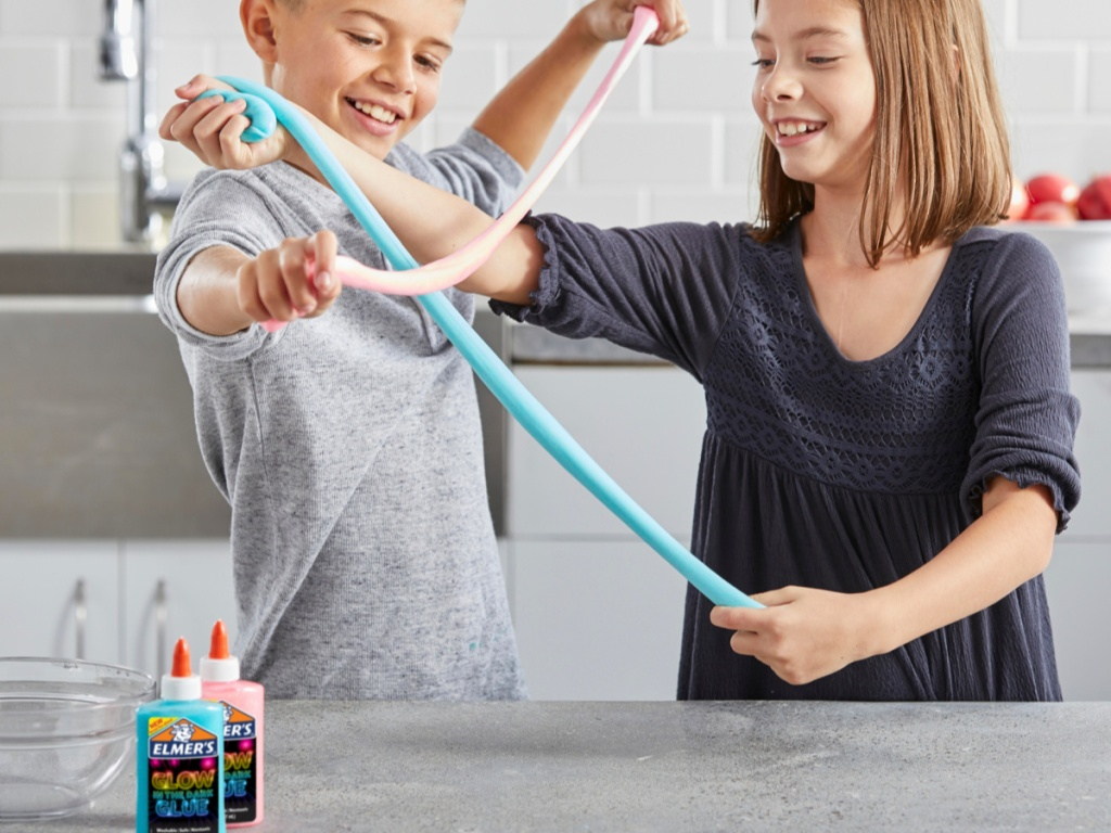boy and girl stretching slime with elmers blue and pink glue on counter