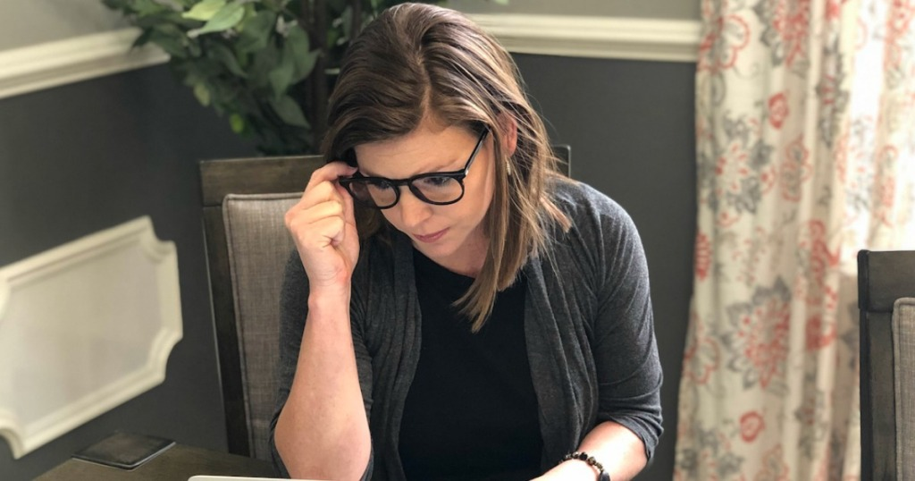 Woman looking at Macbook while wearing black framed glasses