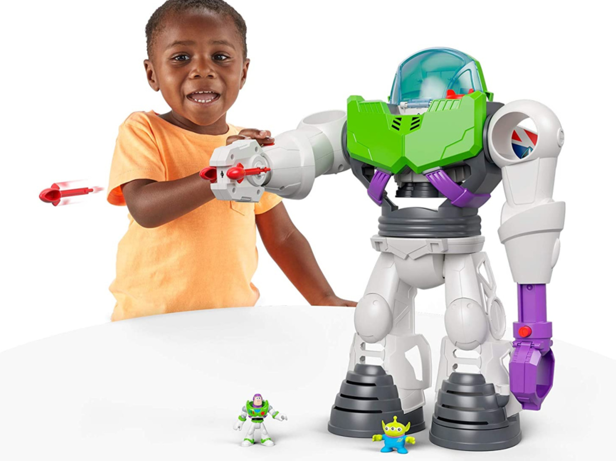 young boy playing with robot toy on white table