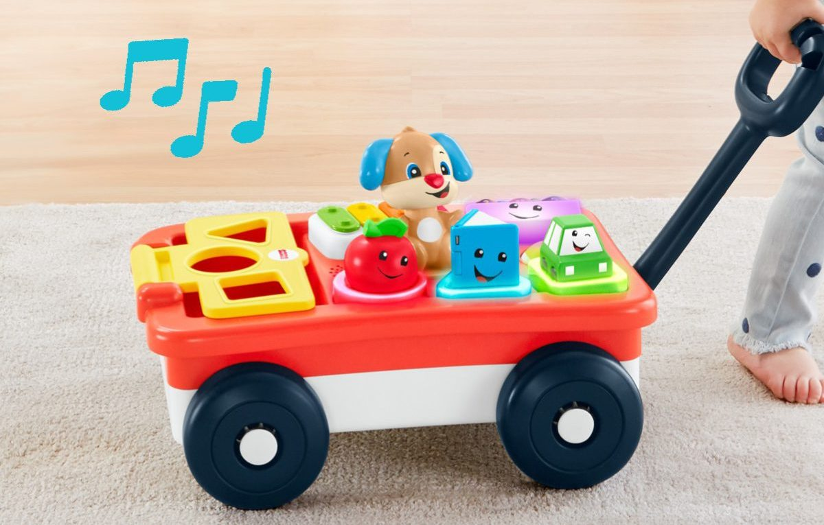young child playing with and rolling toy wagon