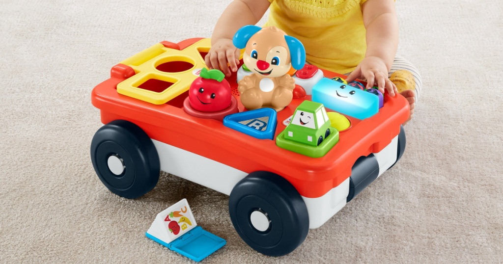 young child playing with toy wagon