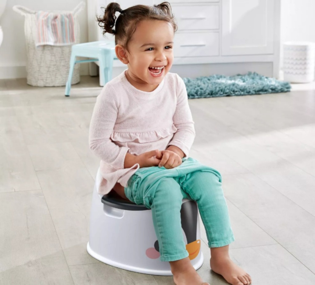 little girl sitting on a Fisher-Price potty