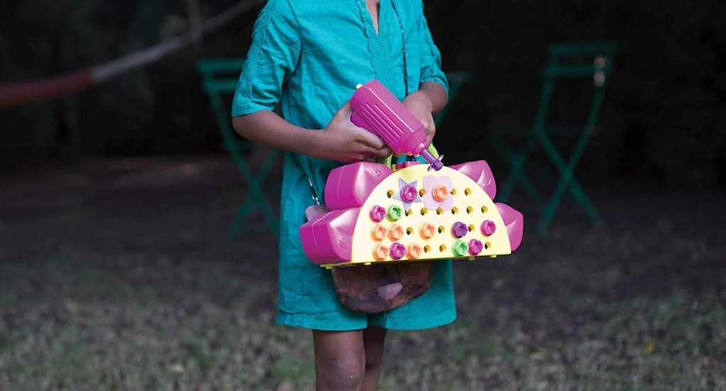 girl carrying a drill set