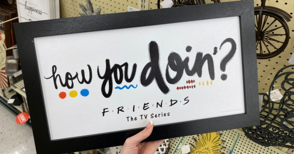 woman hand holding Friend's How You Doin Sign in hobby lobby
