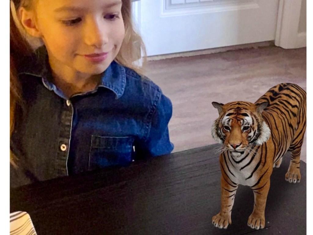 Girl staring at tiger on desk