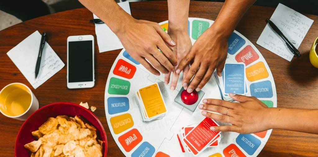 hands pushing a buzzer on a board game