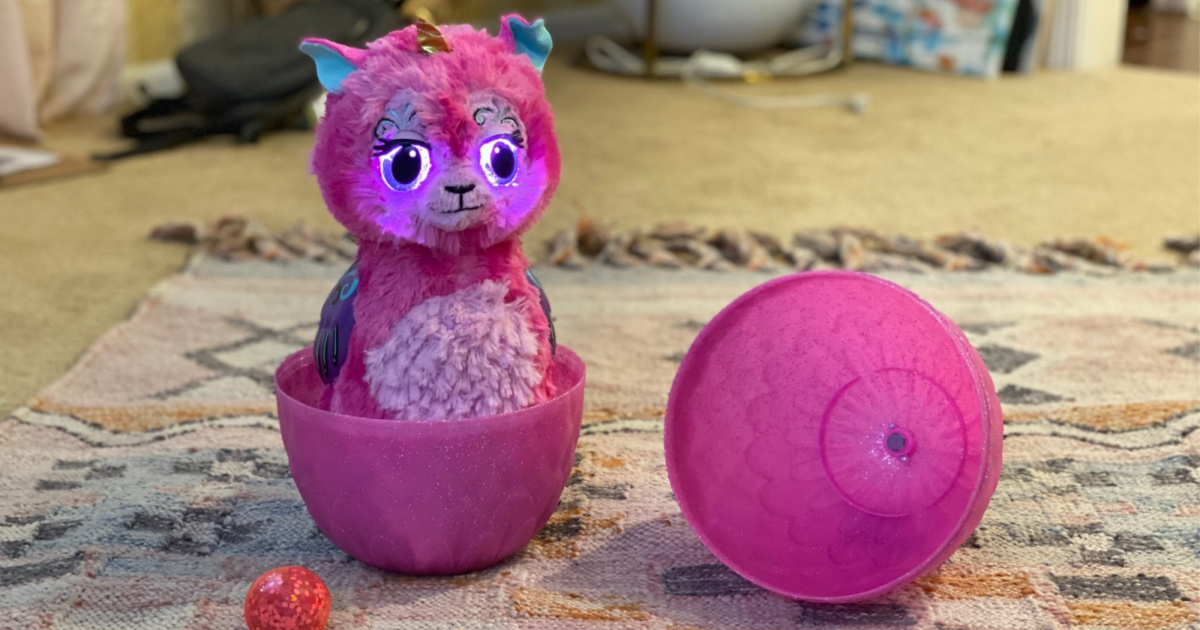 pink llama unicorn hatching toy on carpet in home