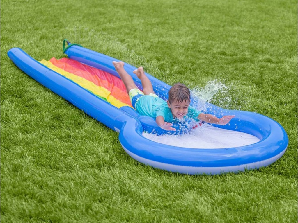 boy sliding down HearthSong Inflatable Water Slide & Board
