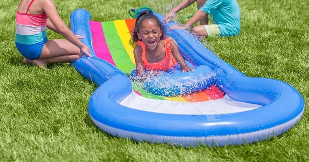 girl sliding on HearthSong Inflatable Water Slide & Board