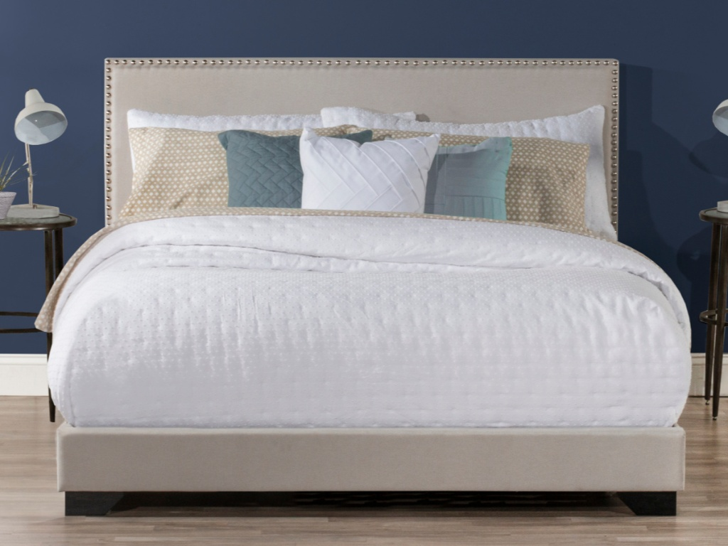 tan bed with white bedding and blue wall