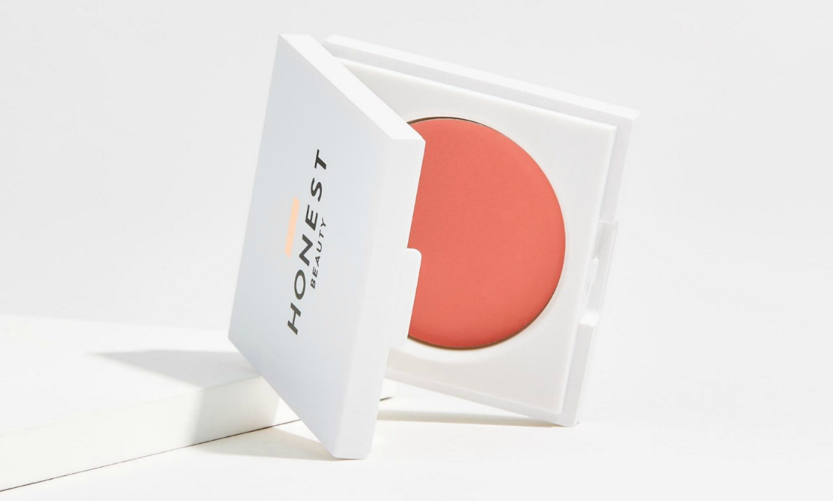 Small container of creme blush in pink color on white surface