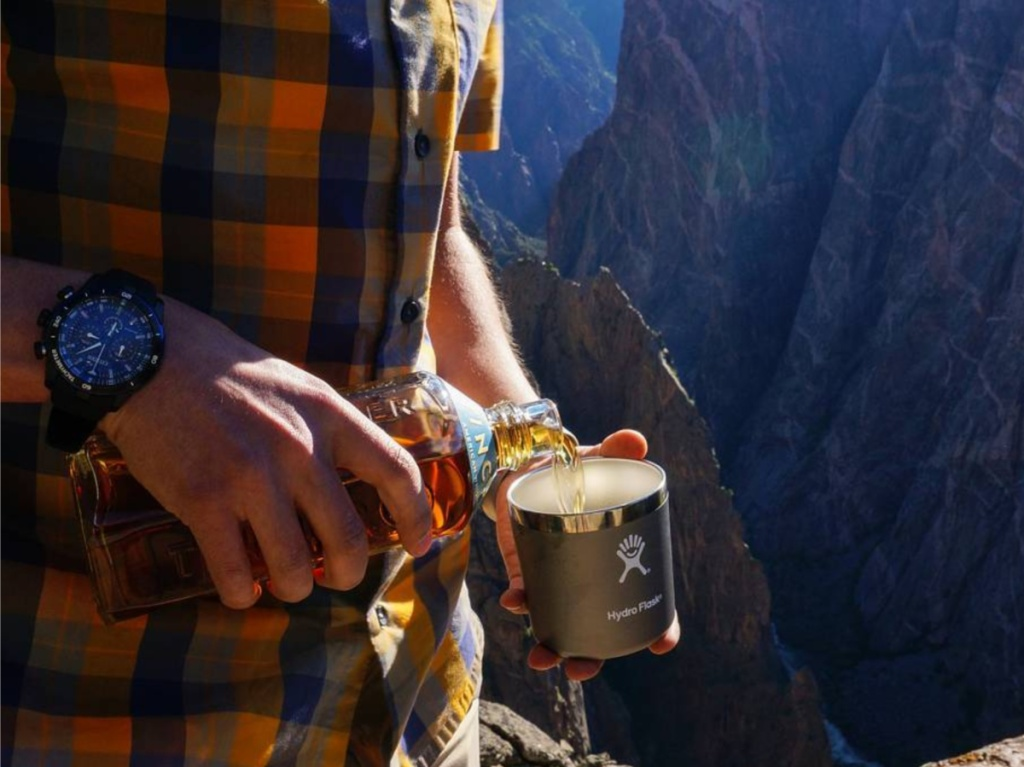 man pouring liquid into tumbler with mountain landscape in background