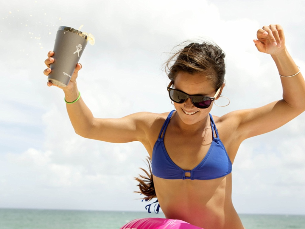 Girl on the beach holding a hydro flask 16 oz tumbler