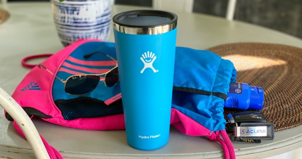 Hydro Flask tumbler next to sunglasses and sports bag
