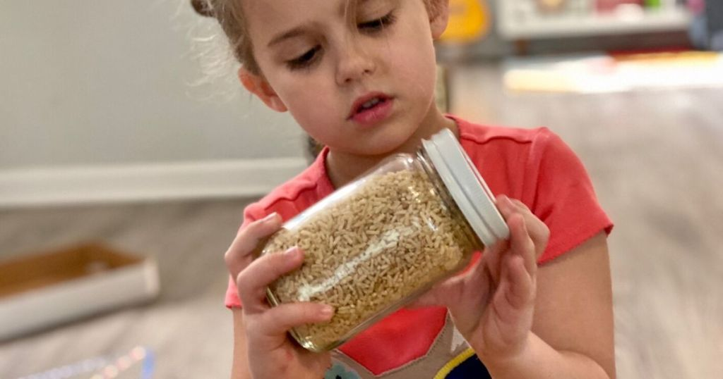 Little girl looking for items in DIY I-Spy jar
