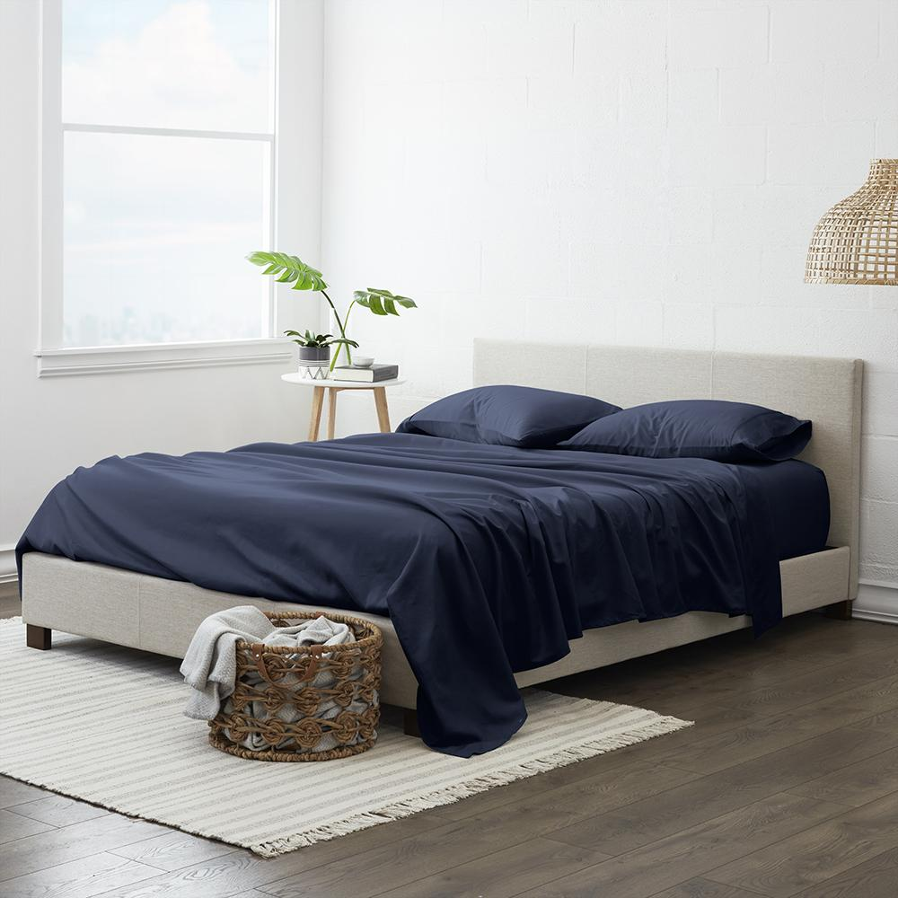 bed made with only sheets with rub and basket in front