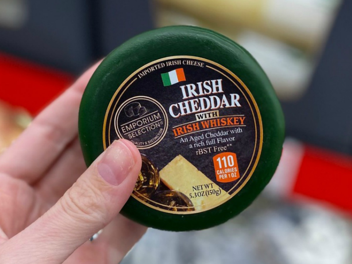 Woman's hand holding a small wheel of Irish cheese near in-store dairy display