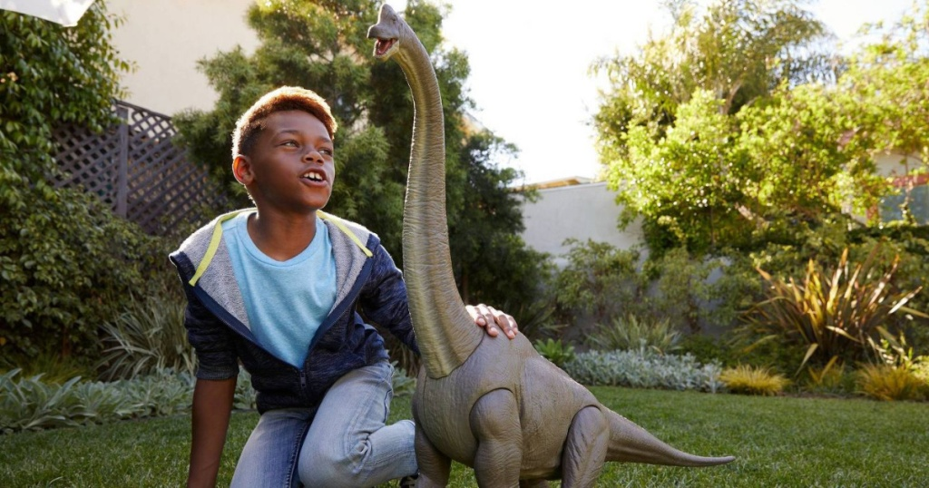 boy playing with large dinosaur toy outside